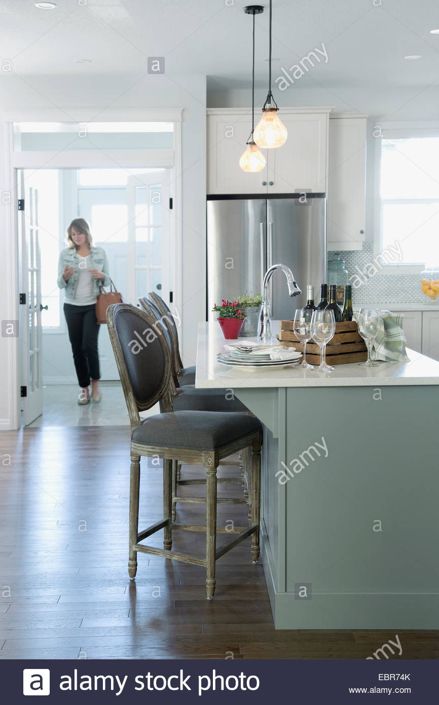 Woman walking into kitchen - Stock Image
