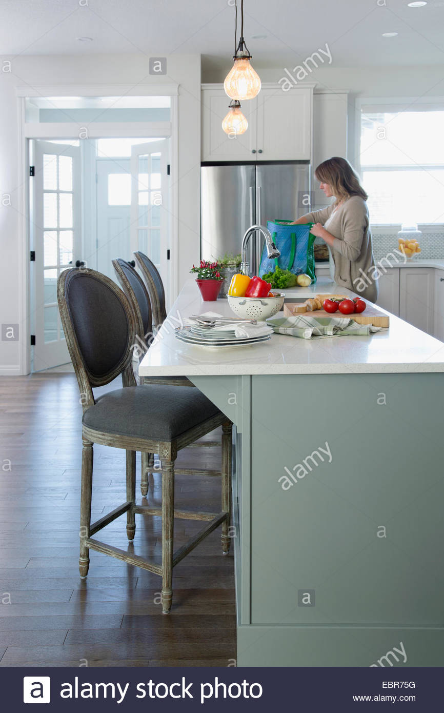 Woman unpacking groceries from reusable bag in kitchen - Stock Image