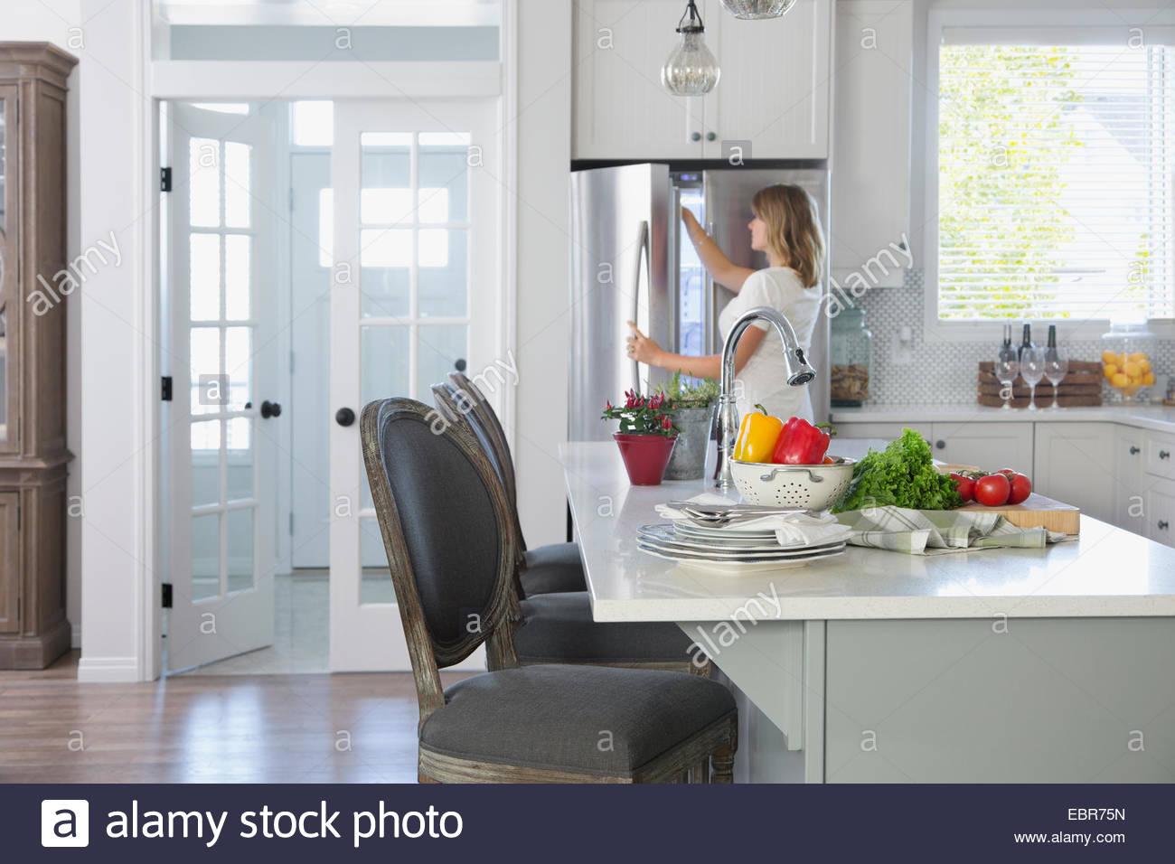 Woman opening freezer door in kitchen - Stock Image