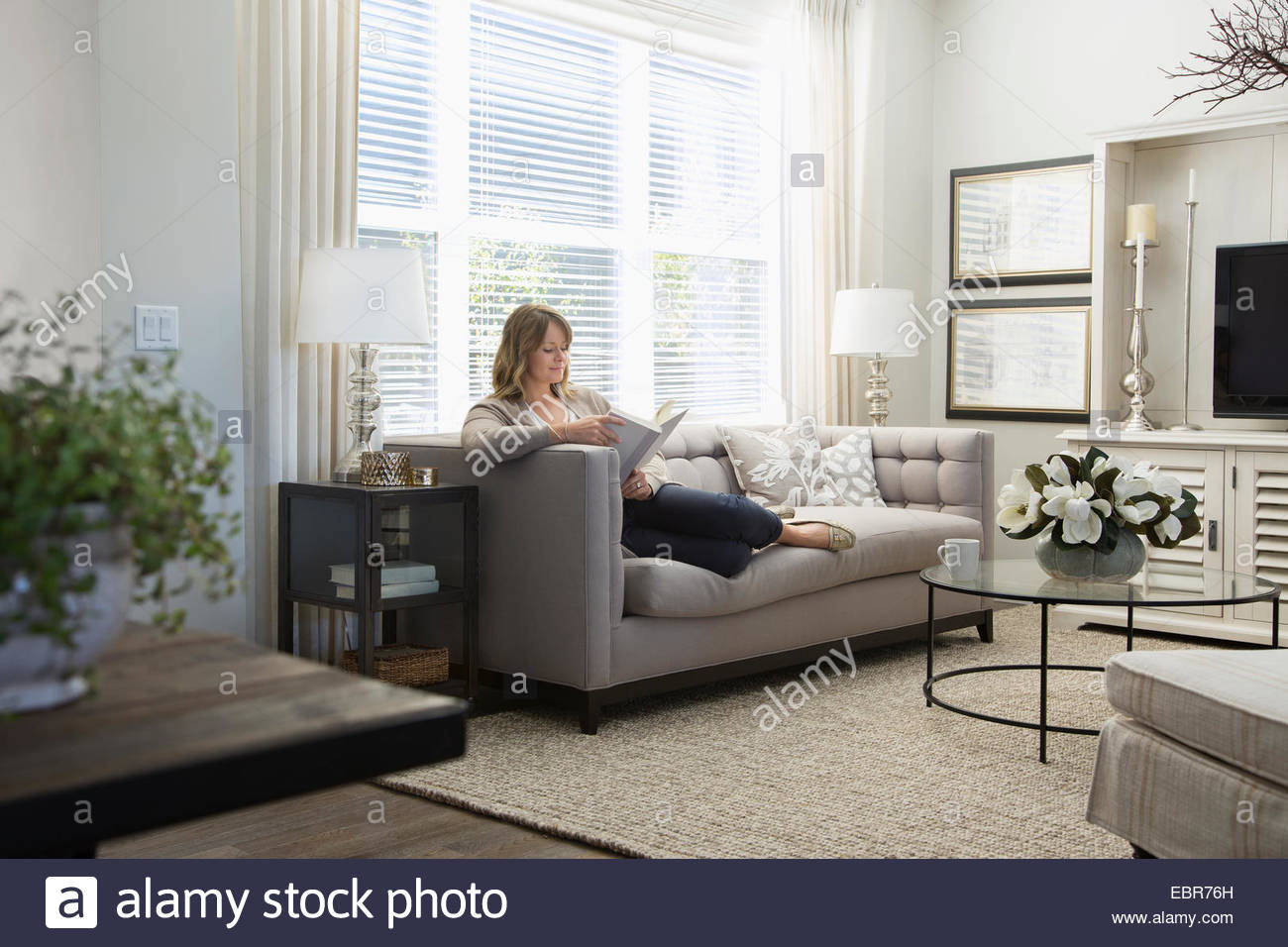 Superior Woman Reading Book On Sofa In Living Room