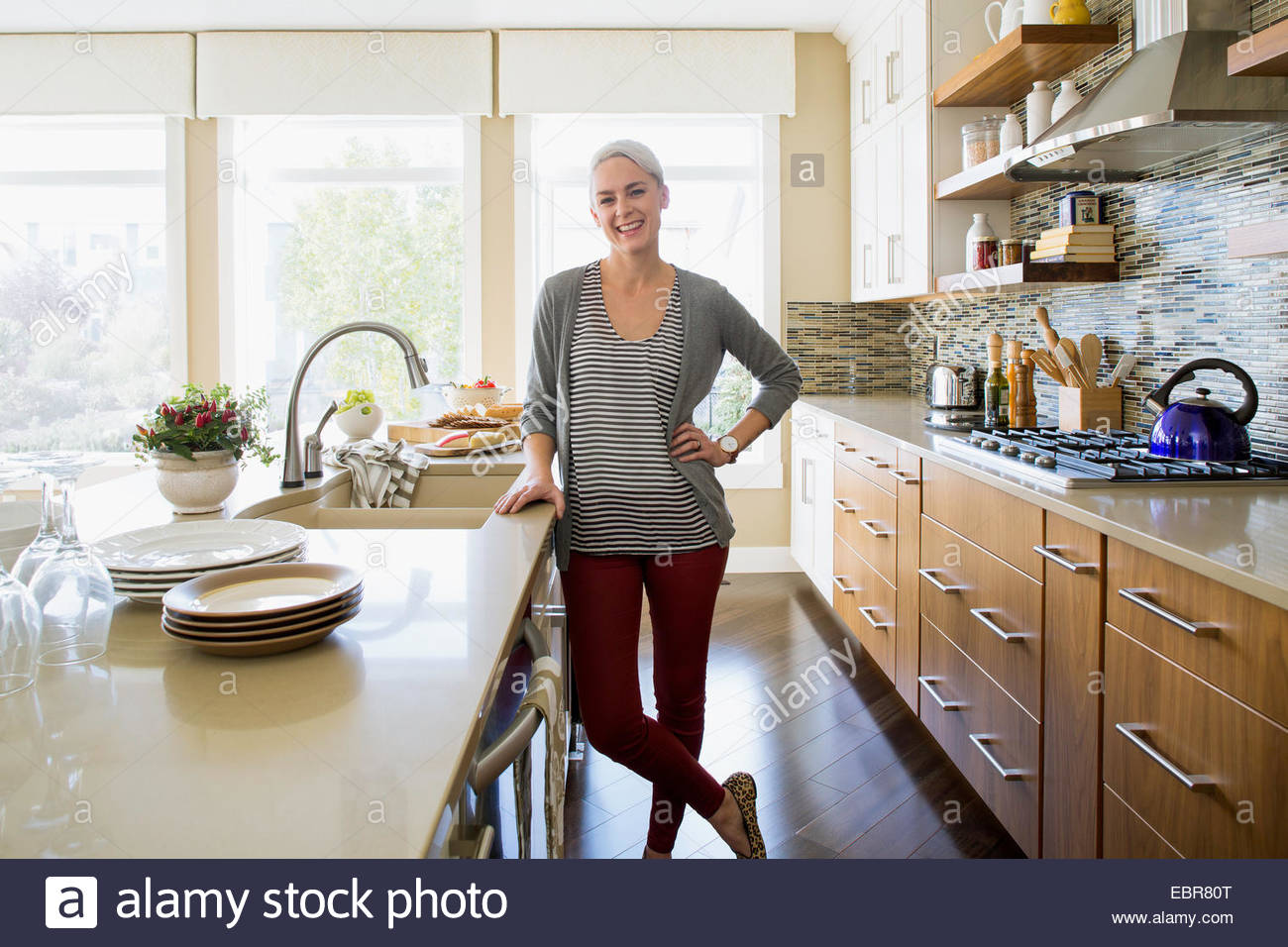Portrait of smiling woman in kitchen Stock Photo