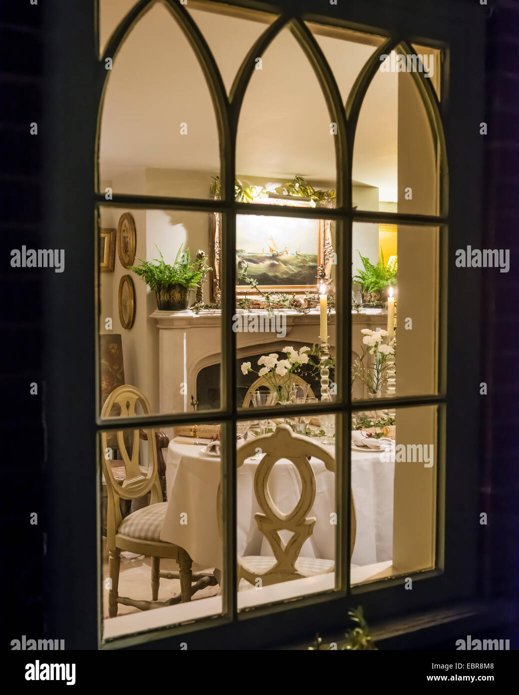 View looking through window to table laid for christmas dinner - Stock Image
