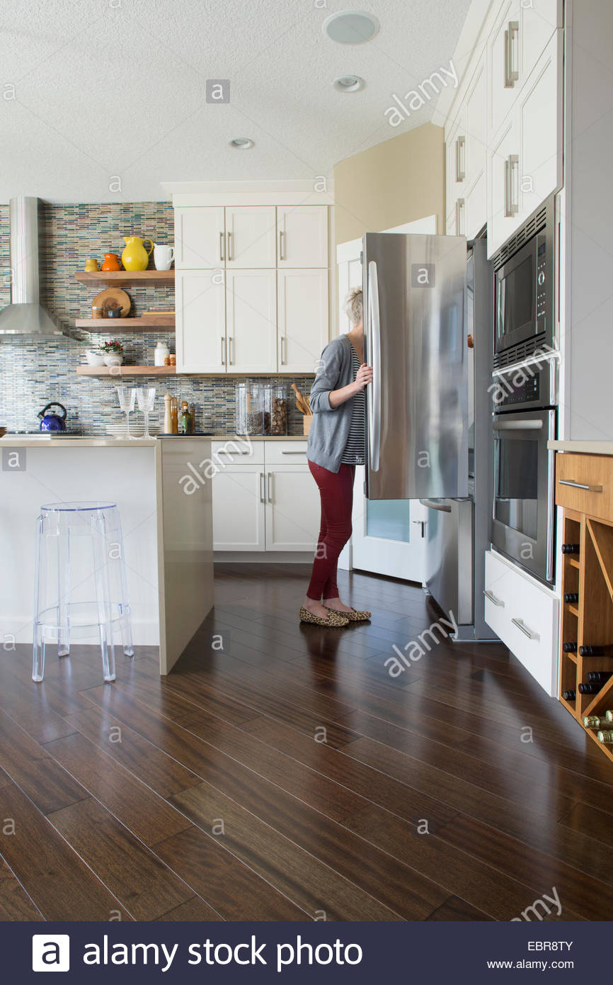 Woman peering into refrigerator in kitchen - Stock Image