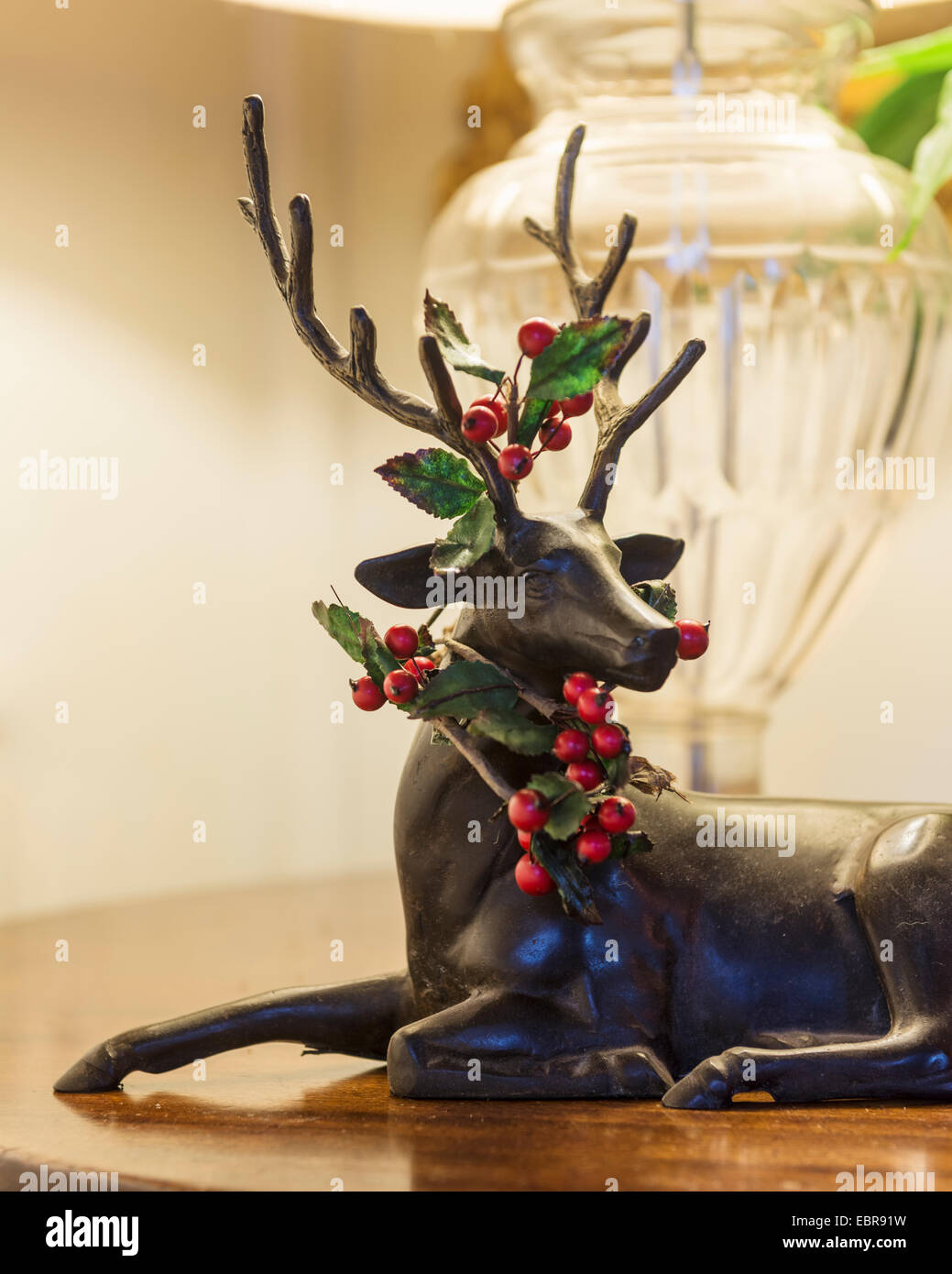 Sprigs of holly adorn a small sculpture of a stag - Stock Image