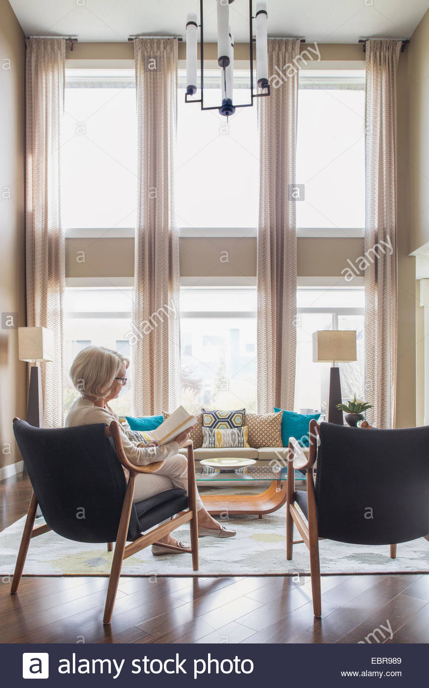 Woman reading book in modern living room - Stock Image