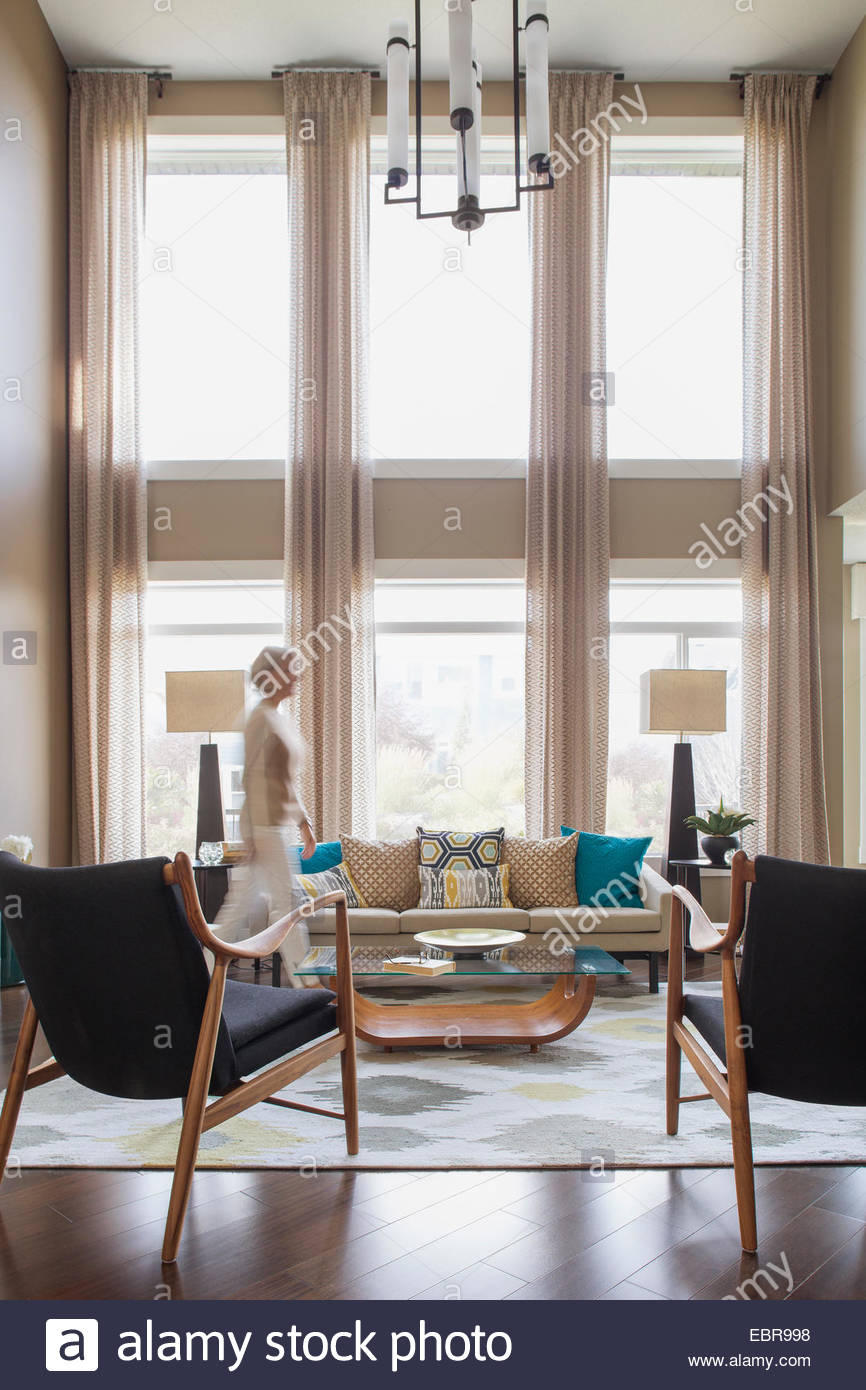 Woman walking in modern living room - Stock Image