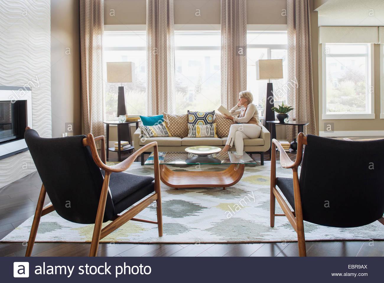 Woman Reading Book On Modern Living Room Sofa