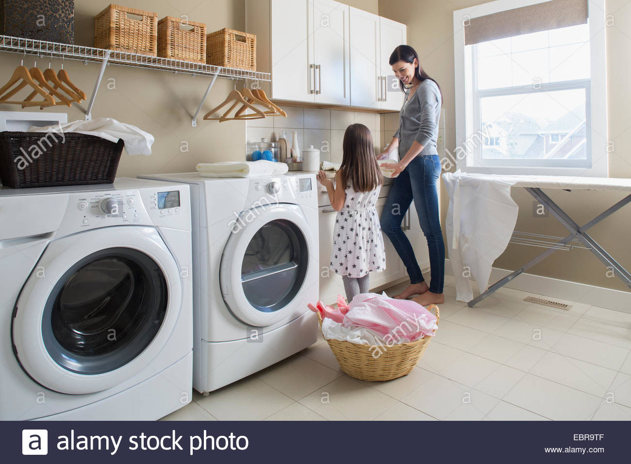 Mother and daughter in laundry room - Stock Image