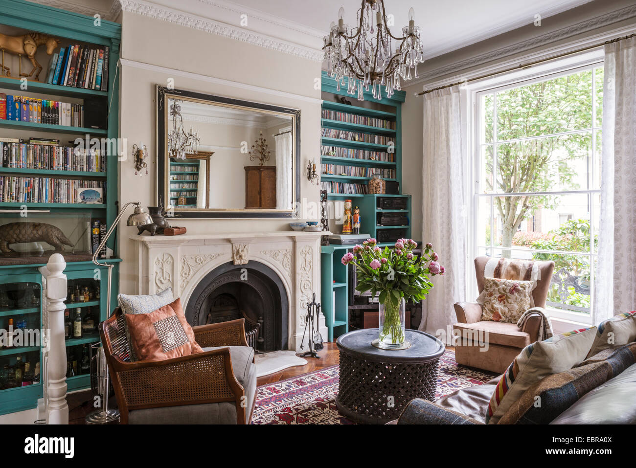 Turquoise shelving in elegant living room with marble fireplace and crystal chandelier - Stock Image