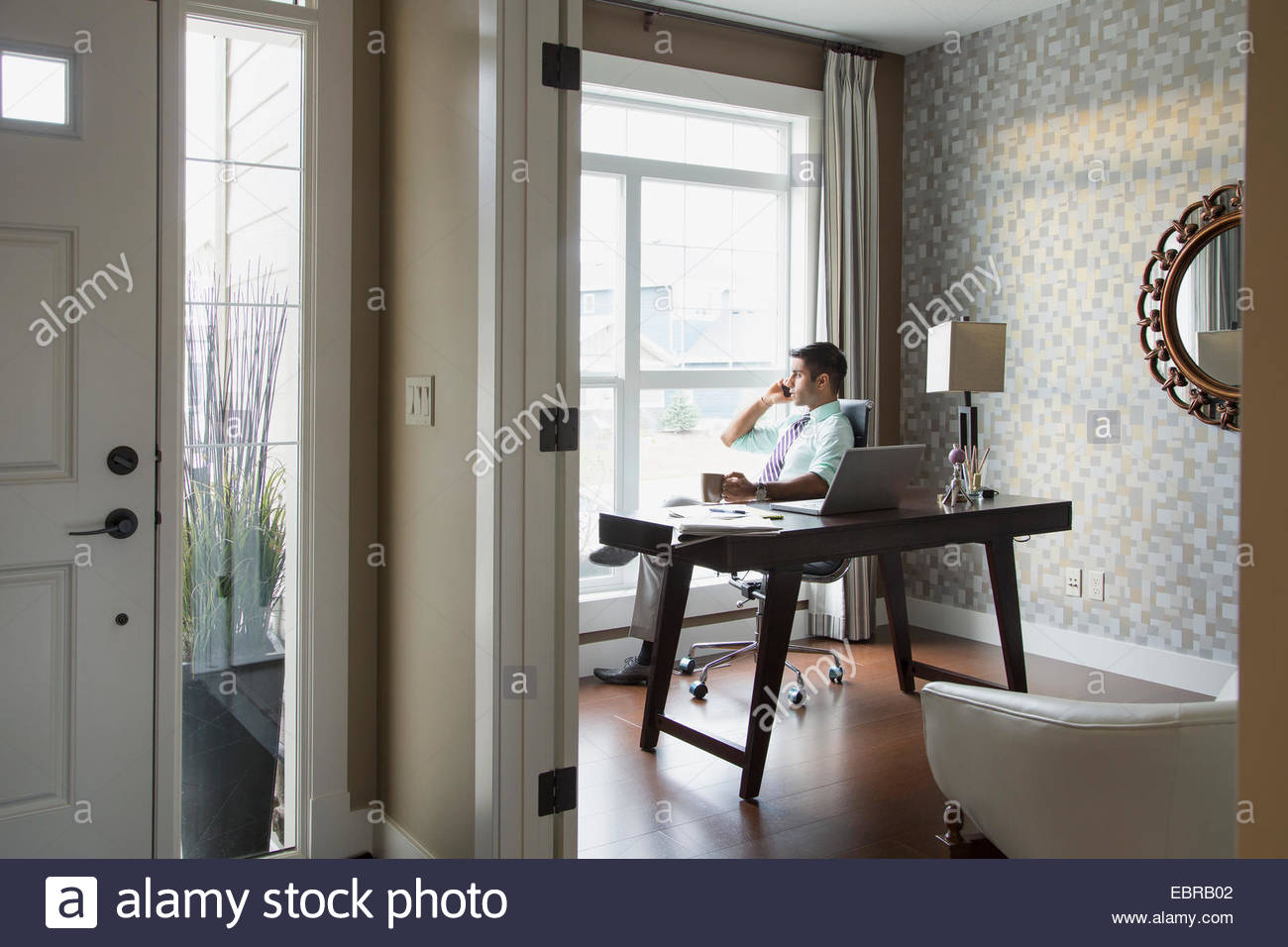 Man talking on cell phone in home office - Stock Image