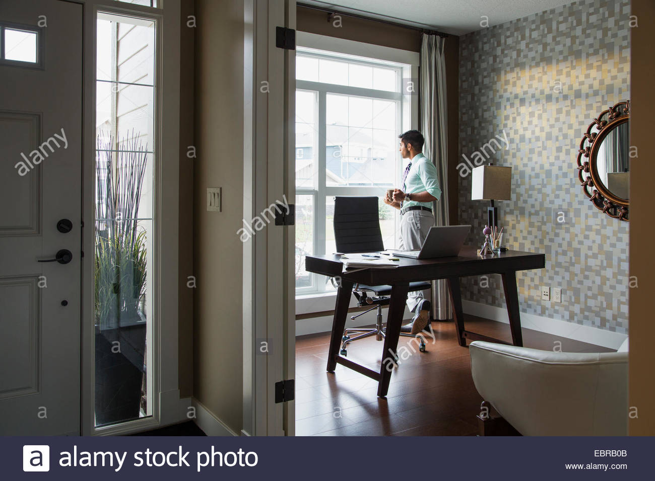 Man drinking coffee at home office window - Stock Image