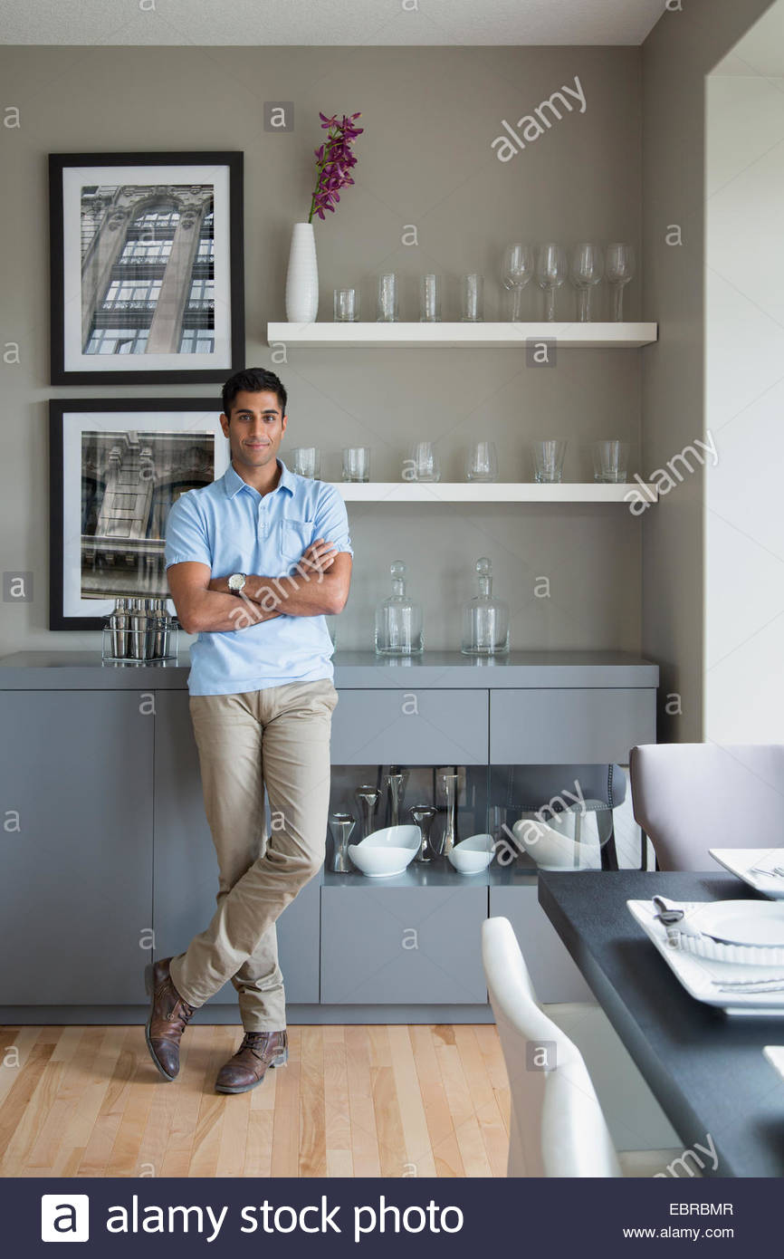 Portrait of confident man in kitchen - Stock Image