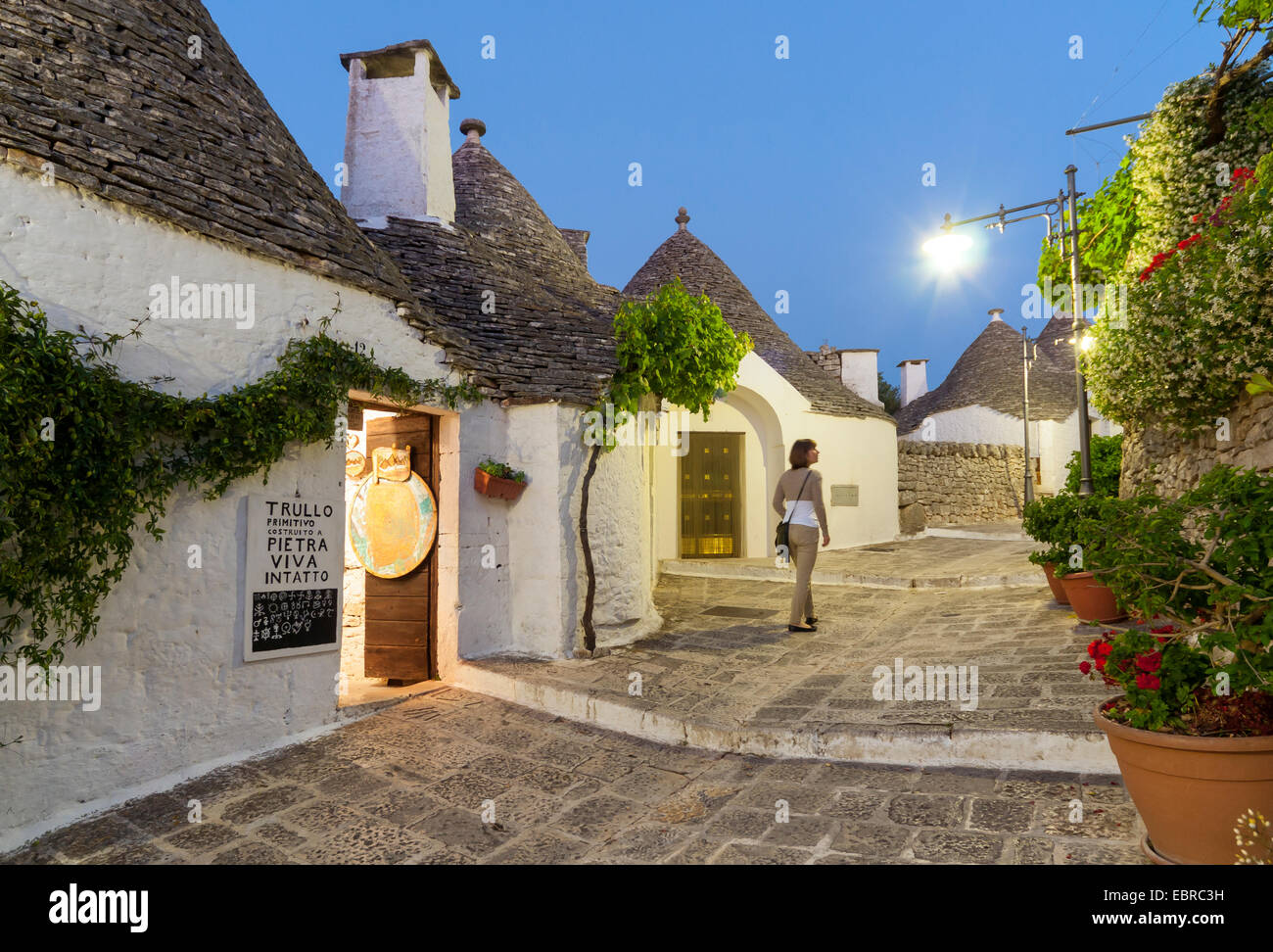 Young Woman walks along Street with Trulli Houses at Night, Alberobello, Puglia, Italy (Model release available Stock Photo