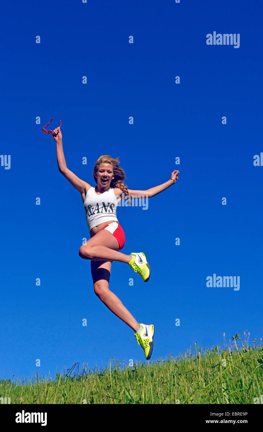 young woman jumping in a meadow, France - Stock Image