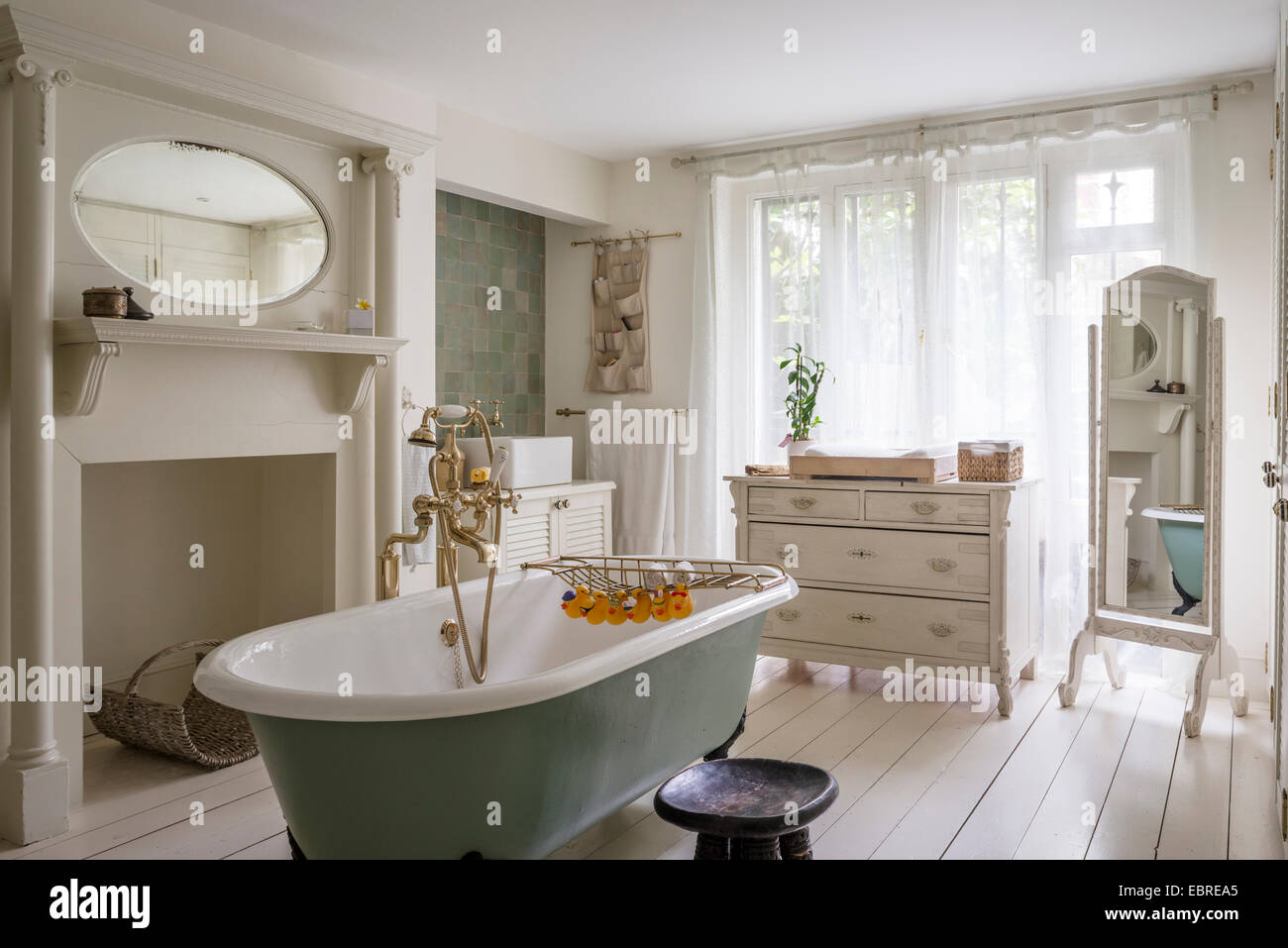 Freestanding roll-top bath with brass fittings in North London home - Stock Image