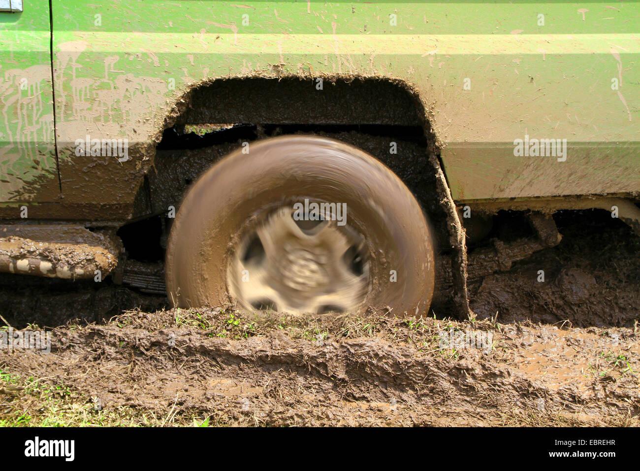 spinning wheel of a safari car sticking in the mud, Tanzania, Serengeti National Park Stock Photo