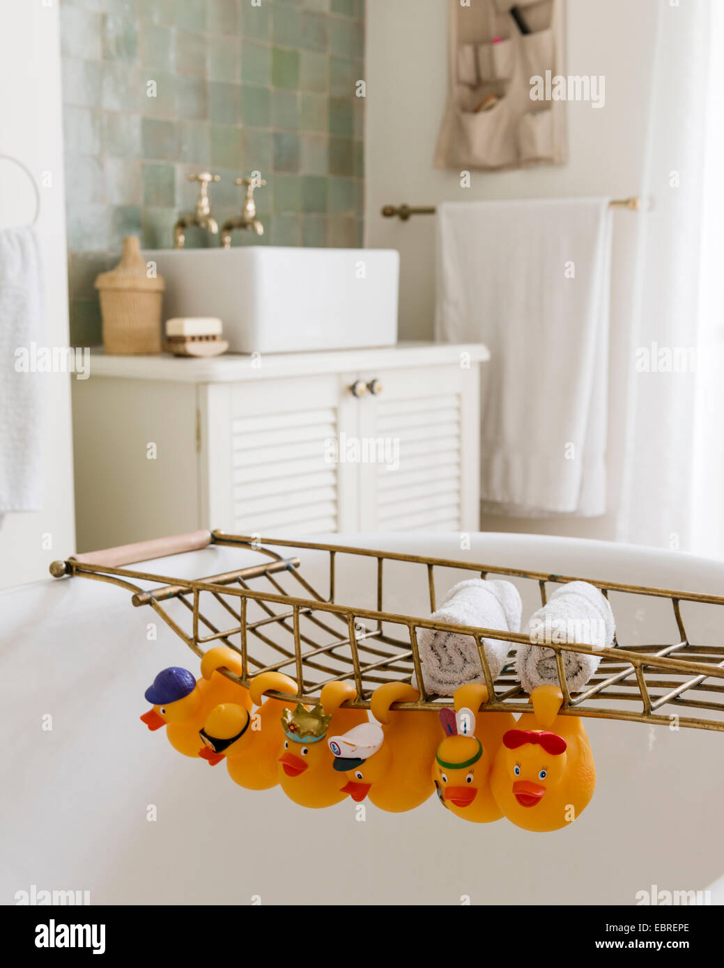 Rubber ducks hang on freestanding roll-top bathrack in North London home - Stock Image