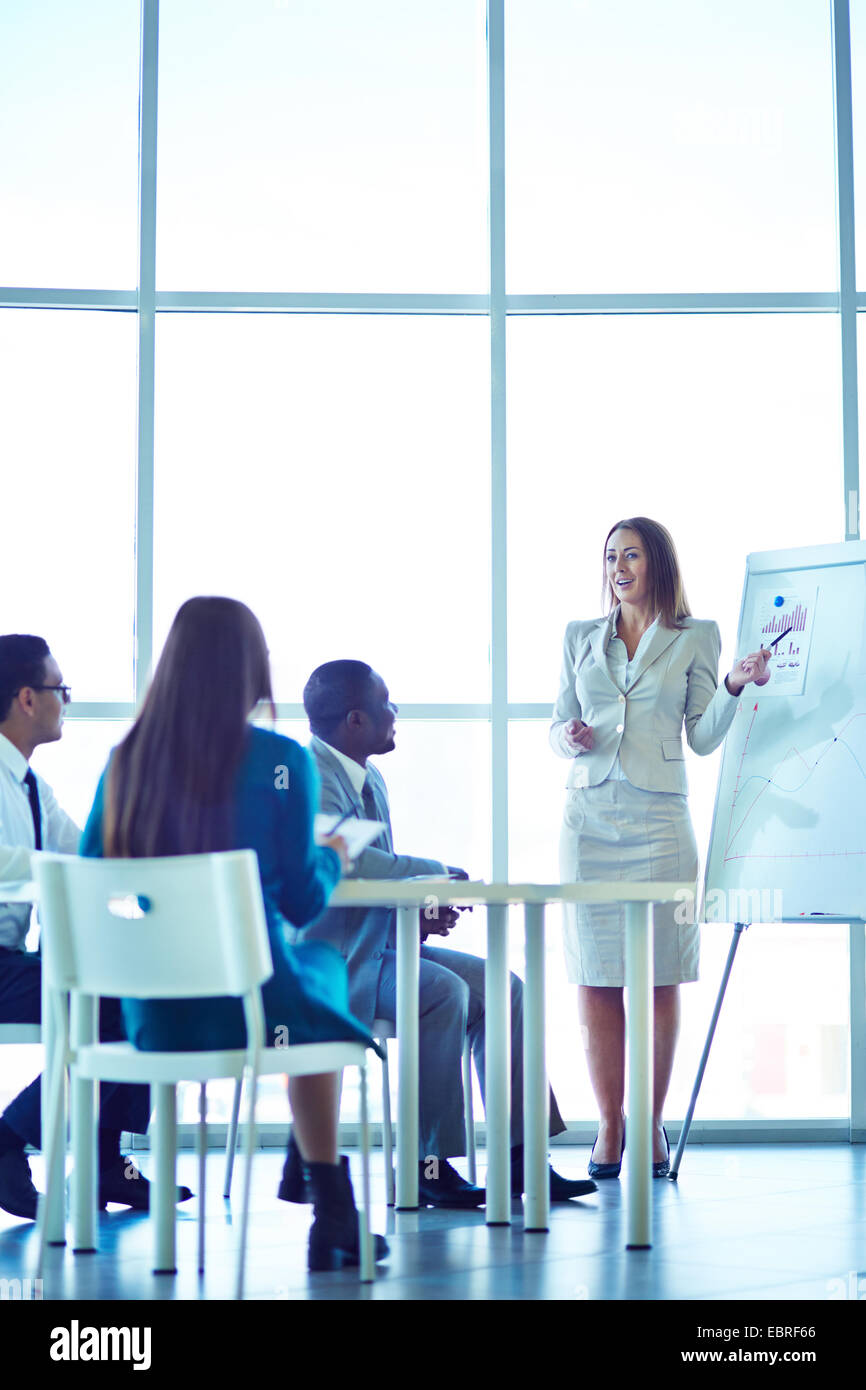 Female leader explaining business strategy - Stock Image