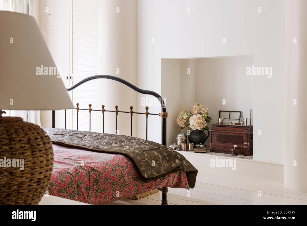 Patterned quilt on metal framed double bed - Stock Image