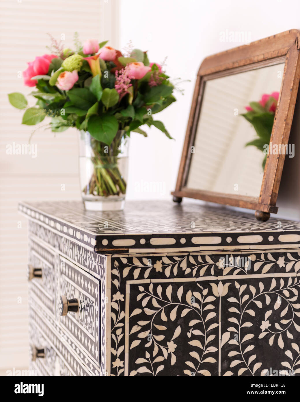 Mirror and vase of flowers on bone inlay chest of drawers - Stock Image