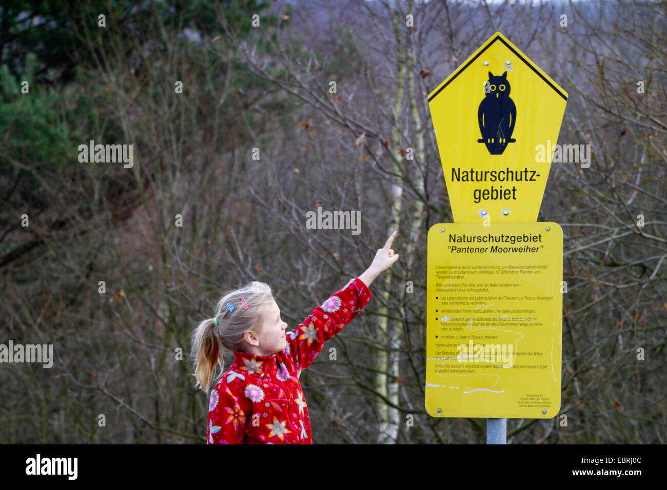 girl pointing at a conservation area sign Pantener Moorweiher, Germany - Stock Image