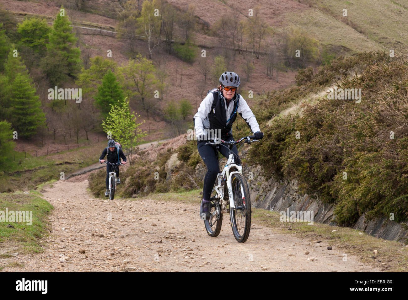 Cycling in the Peak District National Park. Two cyclists on an uphill track on the north side of Jaggers Clough, Stock Photo