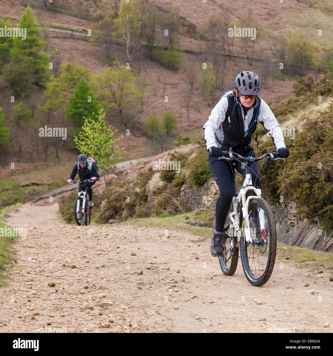 Mountain biking in the UK. Cyclists cycling on an up hill path on the north side of Jaggers Clough, Derbyshire, Stock Photo