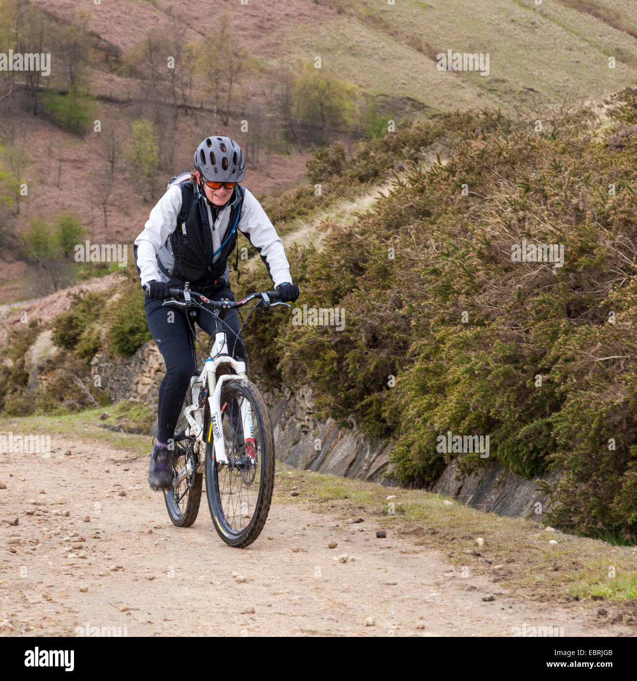 Woman cycling on a path up a hill the north side of Jaggers Clough, Derbyshire, Peak District, England, UK Stock Photo