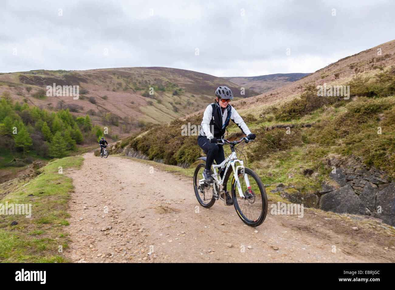 Woman cycling up the stony track on the north side of Jaggers Clough, Derbyshire, Peak District, England, UKStock Photo