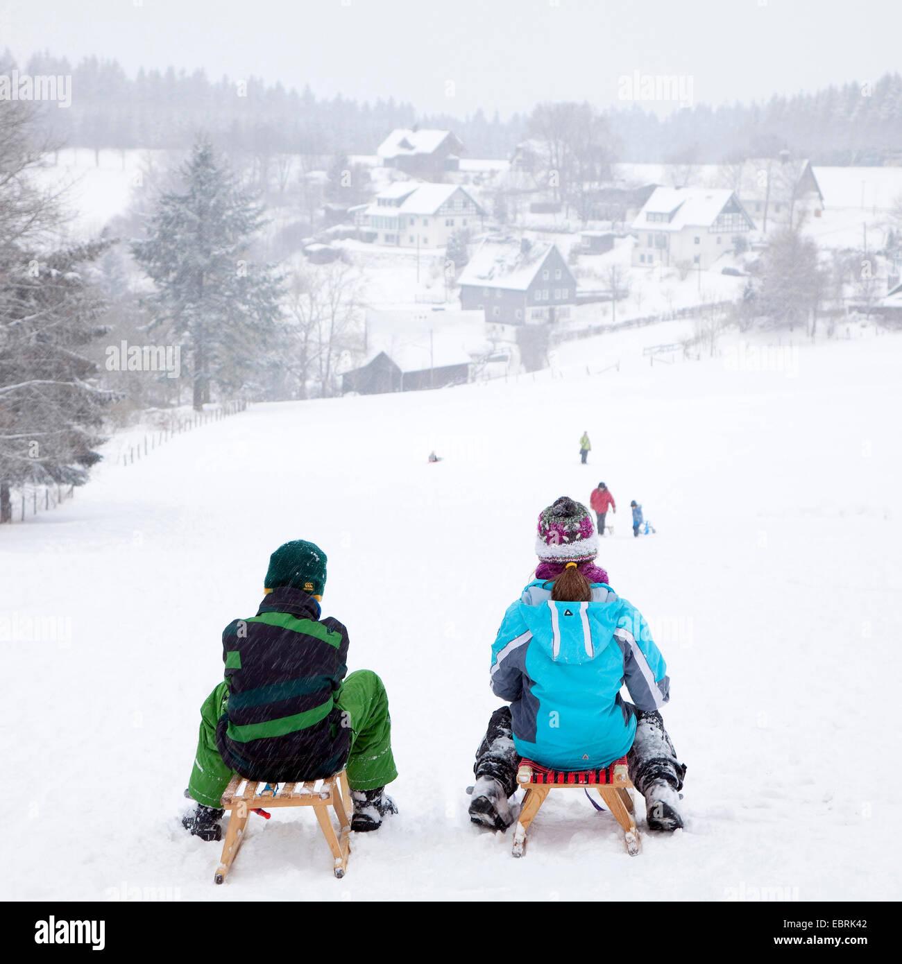 two kids on a piste in snowy landscape in Schanze, Germany, North Rhine-Westphalia, Sauerland, Schmallenberg - Stock Image