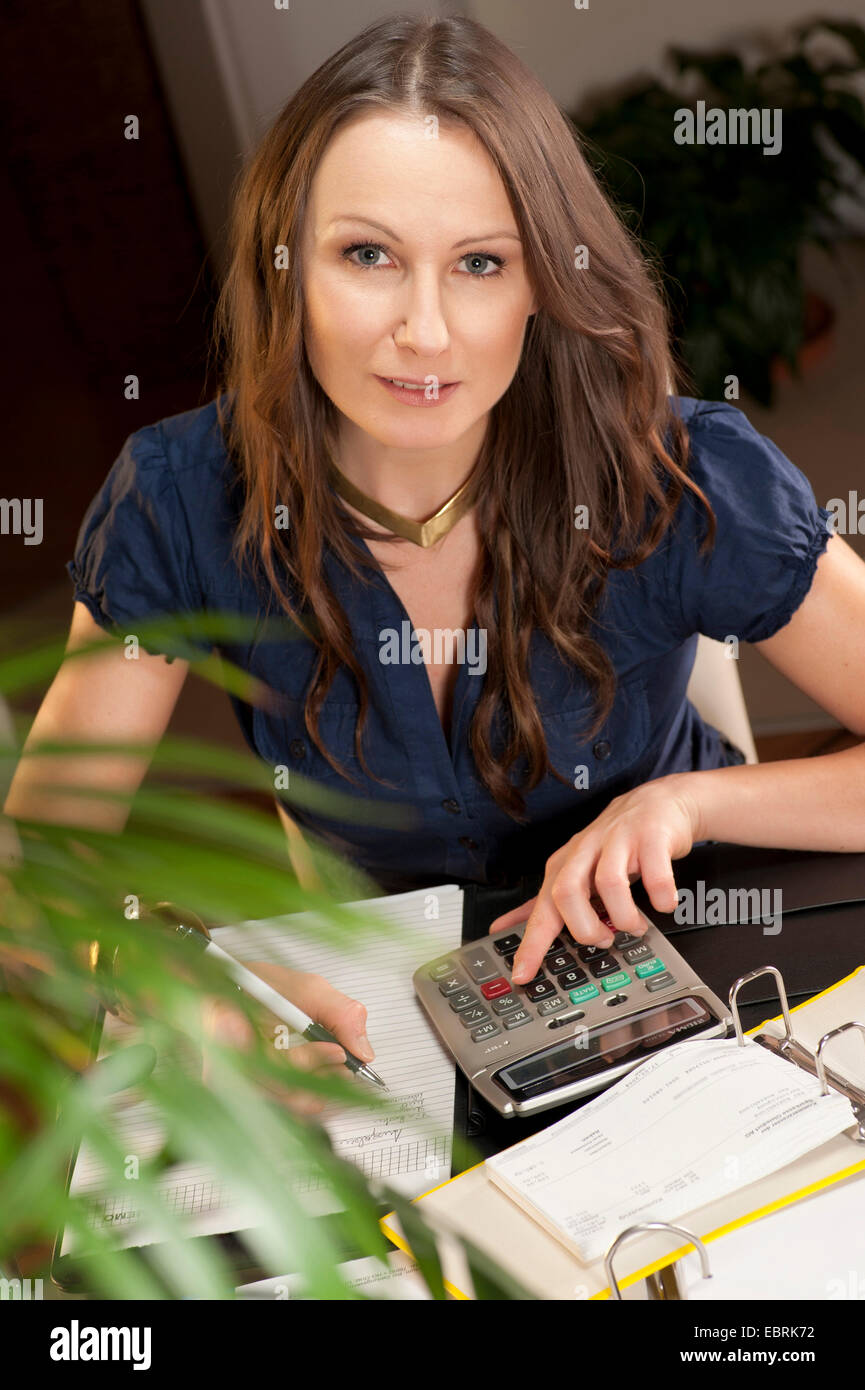 young woman sitting at her desk checking her bank statements - Stock Image
