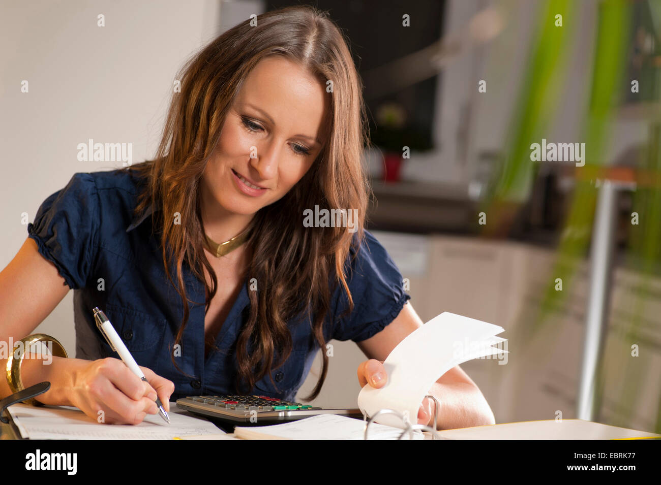 young woman sitting at her desk checking her bank statements with a content smile - Stock Image