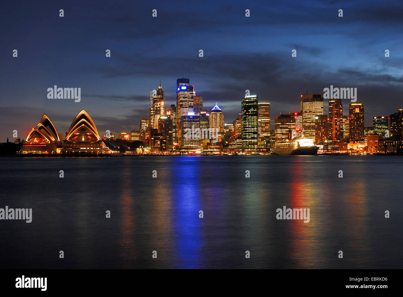 Sydney Opera and Queen Elizabeth 2 ocean liner in front of the skyline of Sydney in evening light, Circular Quay, - Stock Image