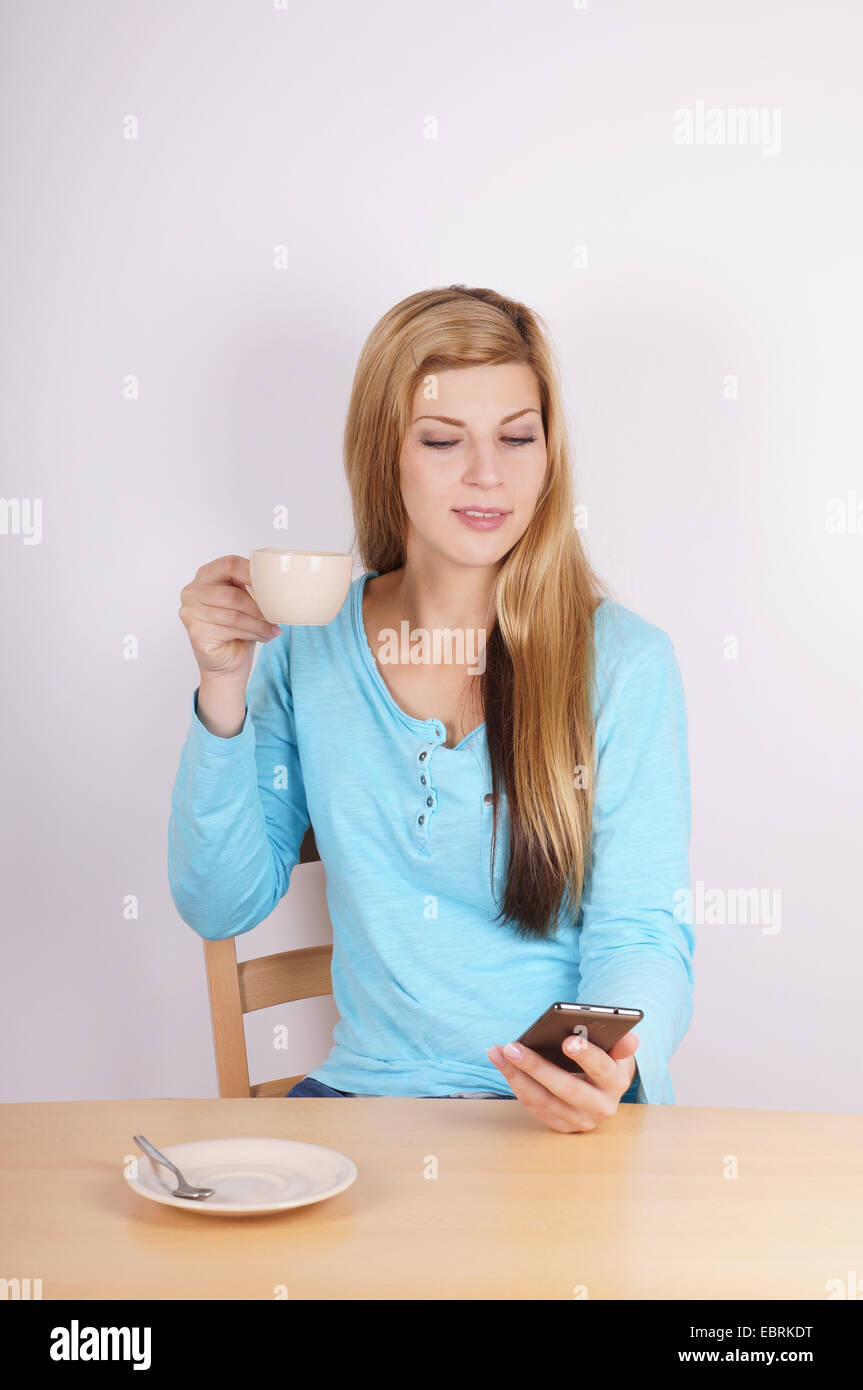 young woman drinking cup of coffee and checking her cell phone - Stock Image