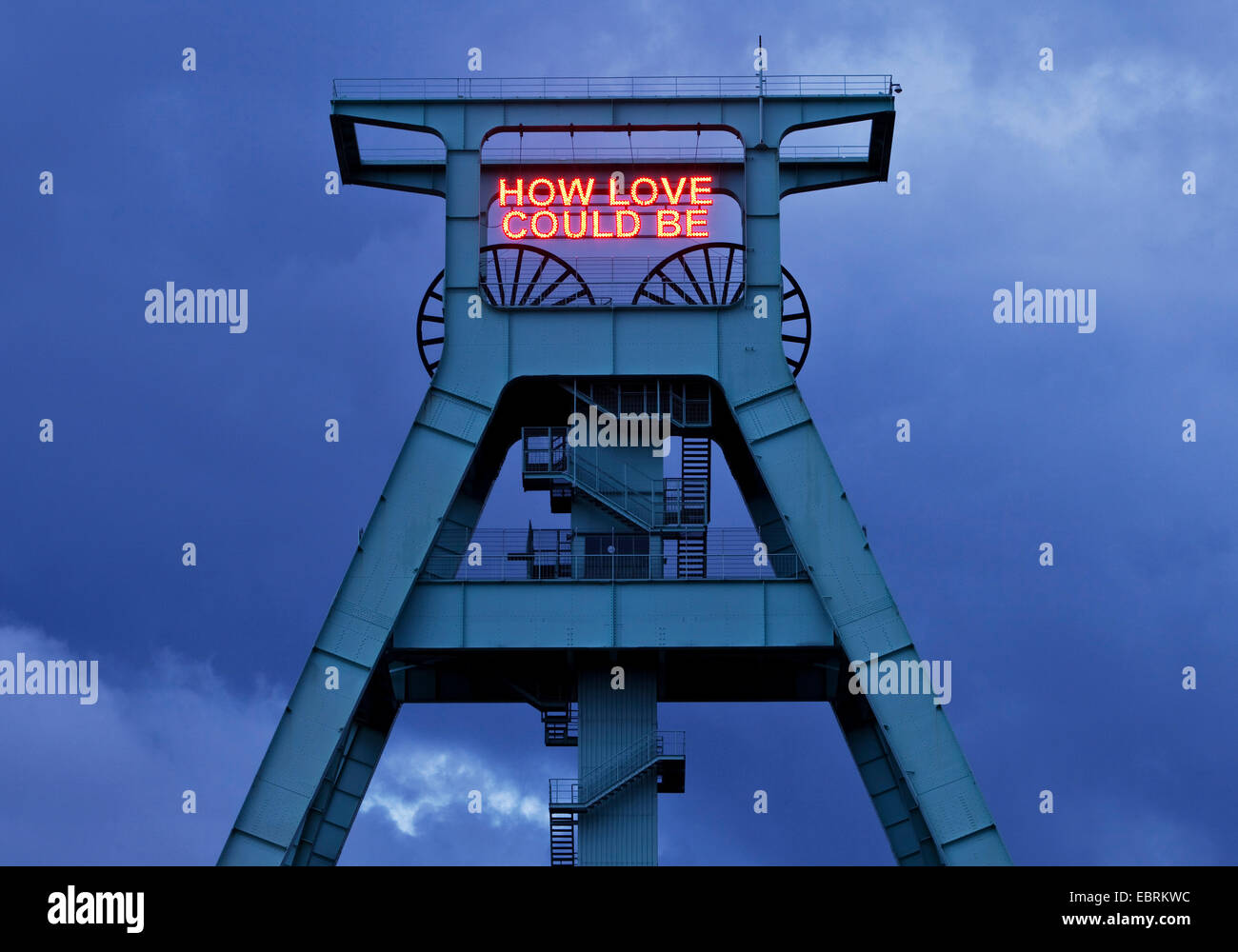illumination HOW LOVE COULD BE on the pit frame of German mining museum, Germany, North Rhine-Westphalia, Ruhr Area, - Stock Image