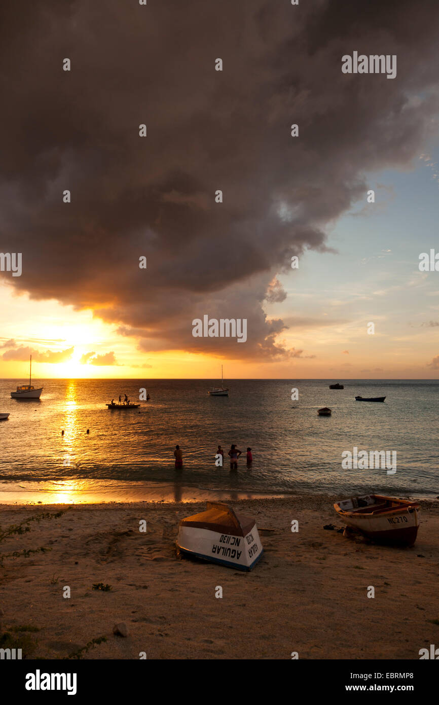 Impressing cloudscape at sunset, Sint Michiel, Curacao. People swimming, boats on beach and moored in the bay. - Stock Image