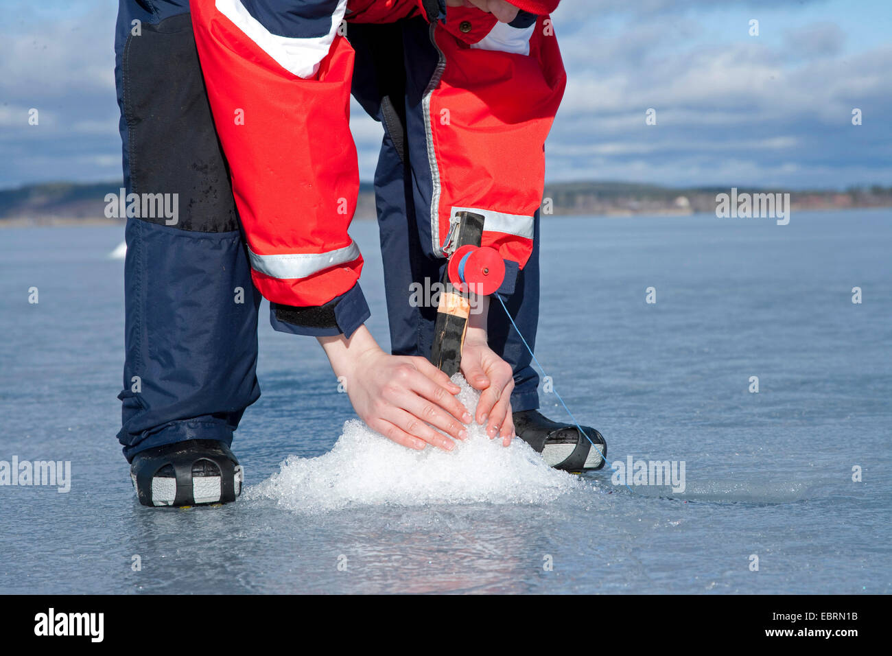 Ice fisher fixing the fishing rod on frozen lake, Sweden - Stock Image