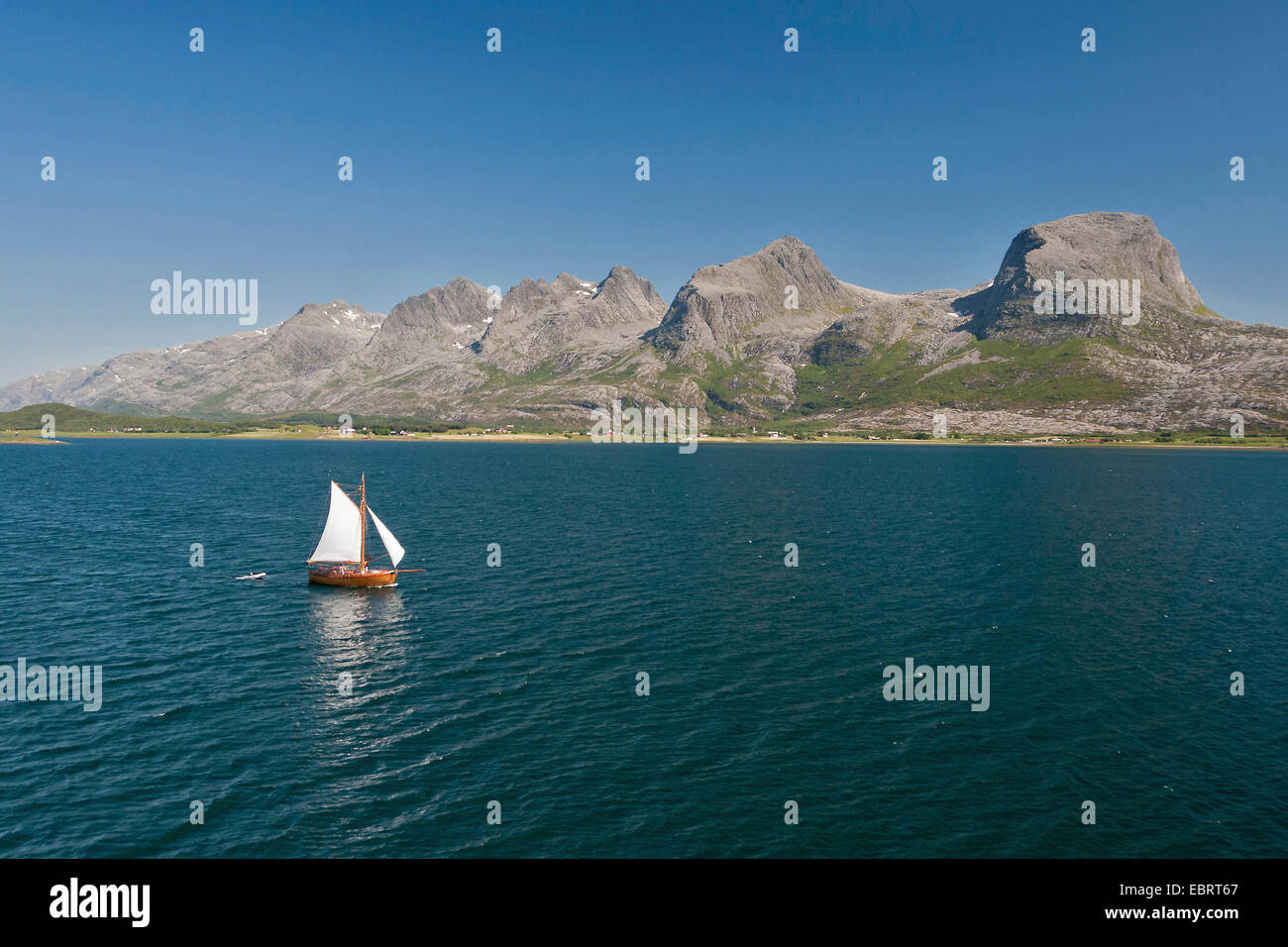 sailboat cruising down Alstenfjorden, In the background are the famous mountain range called the Seven Sisters, - Stock Image