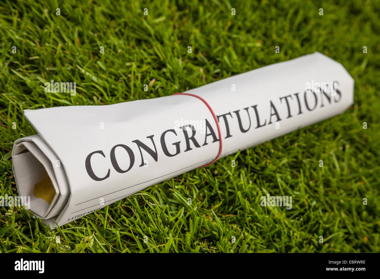 congratulations newspaper on green meadow - Stock Image