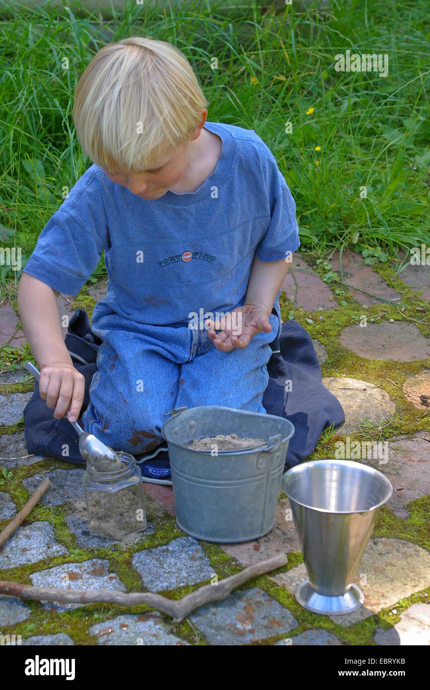 boy mixing soils to paint with earth colour, Germany - Stock Image