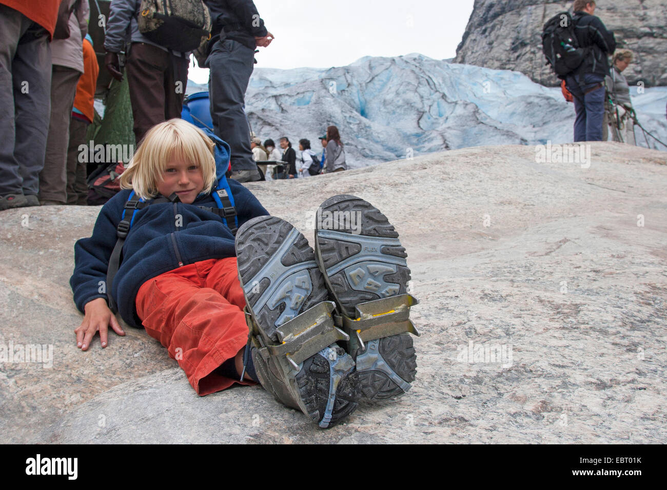 boy applyed ice crampons for glacier travelling, Norway, Jostedalsbreen National Park - Stock Image