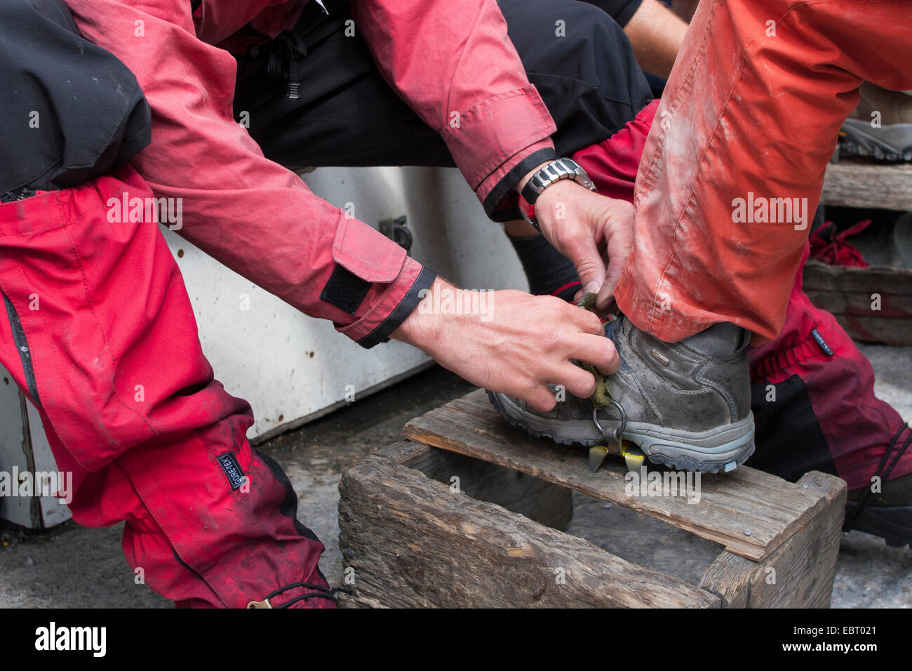 applying ice crampons for glacier travelling, Norway, Jostedalsbreen National Park - Stock Image