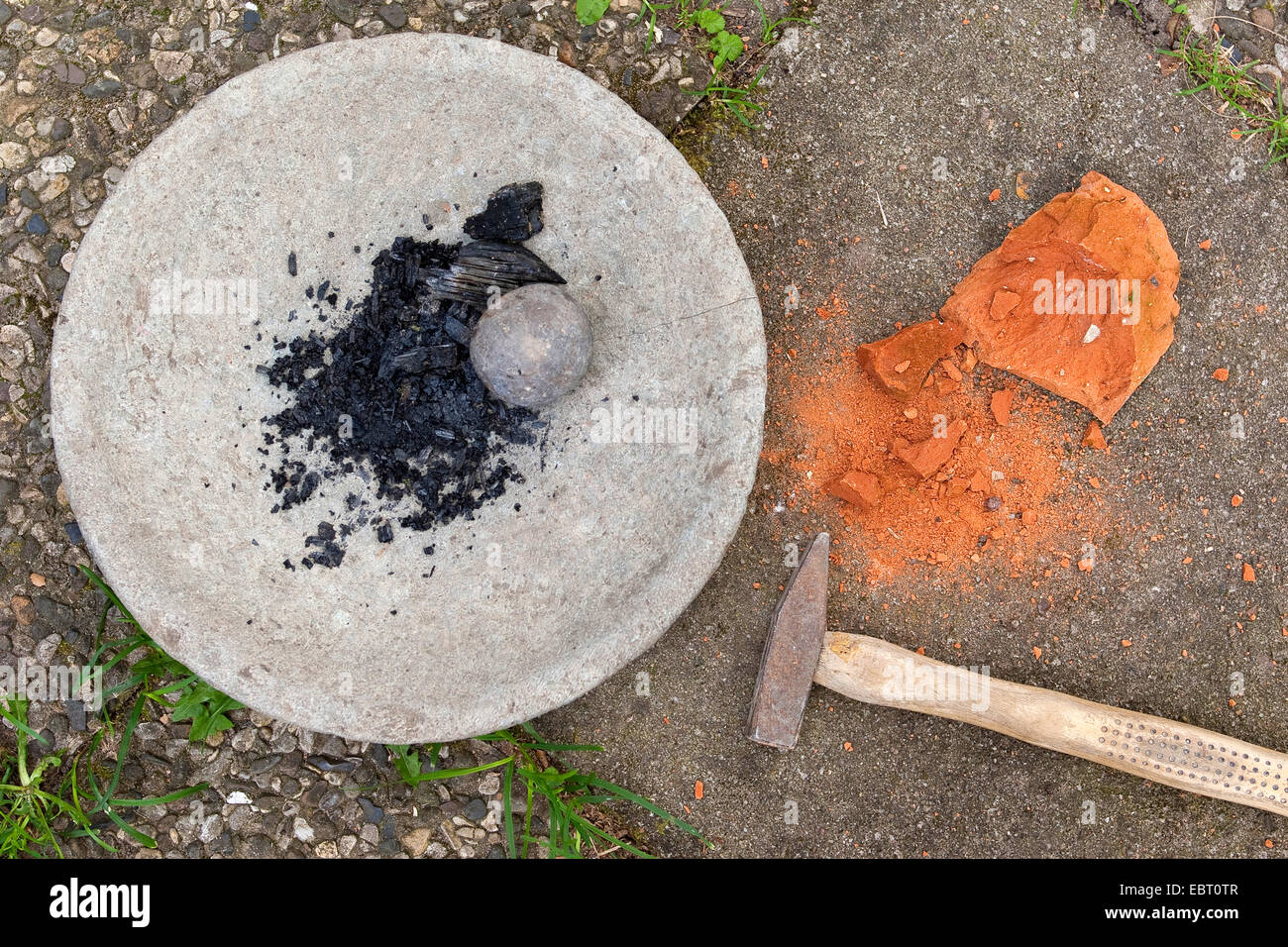 grinding charcoal and crushing red sandstone to paint with earth colour, Germany - Stock Image