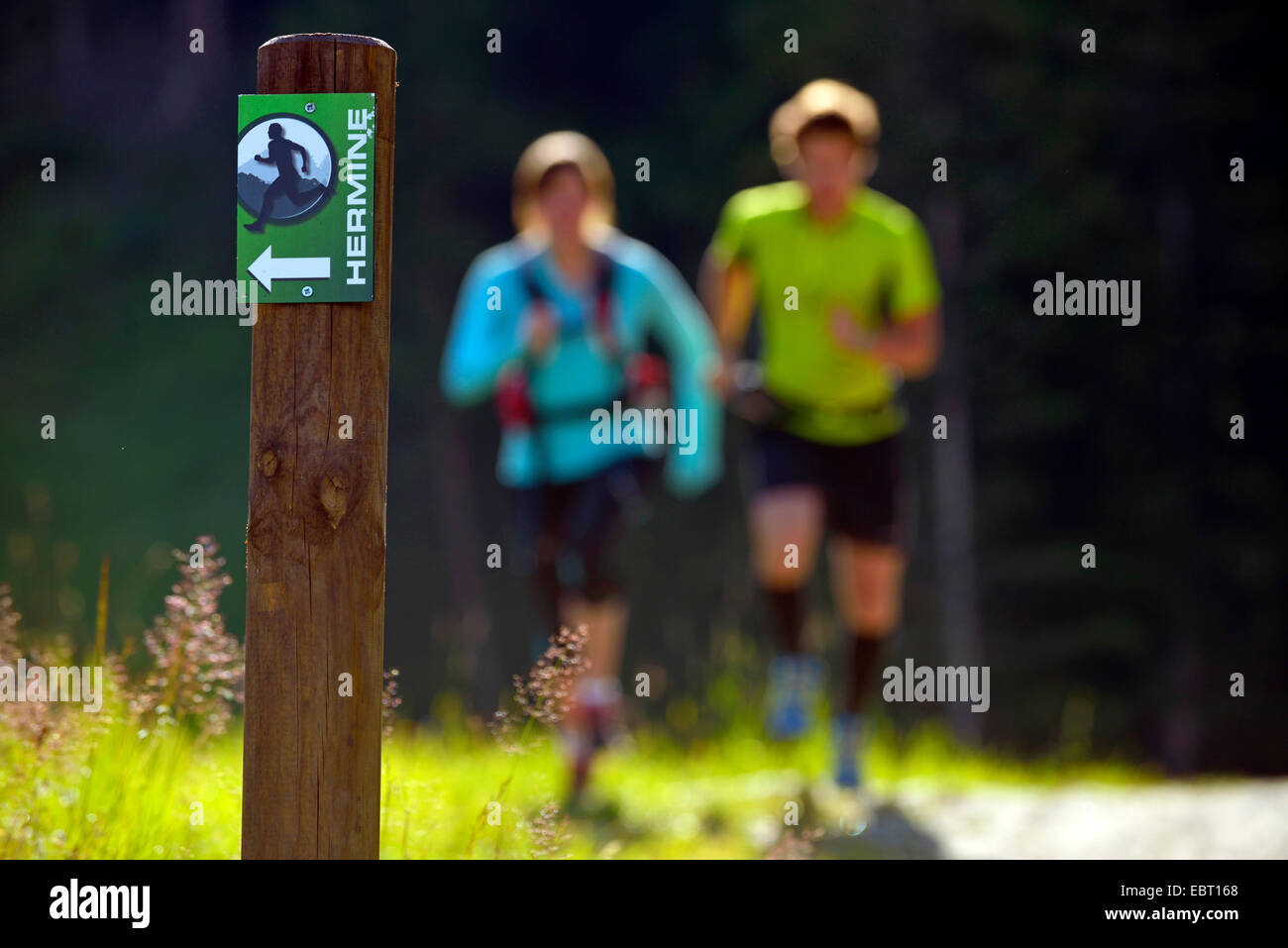 post with hiking sign, two joggers in background, France, Savoie, Sainte Foy Tarentaise - Stock Image
