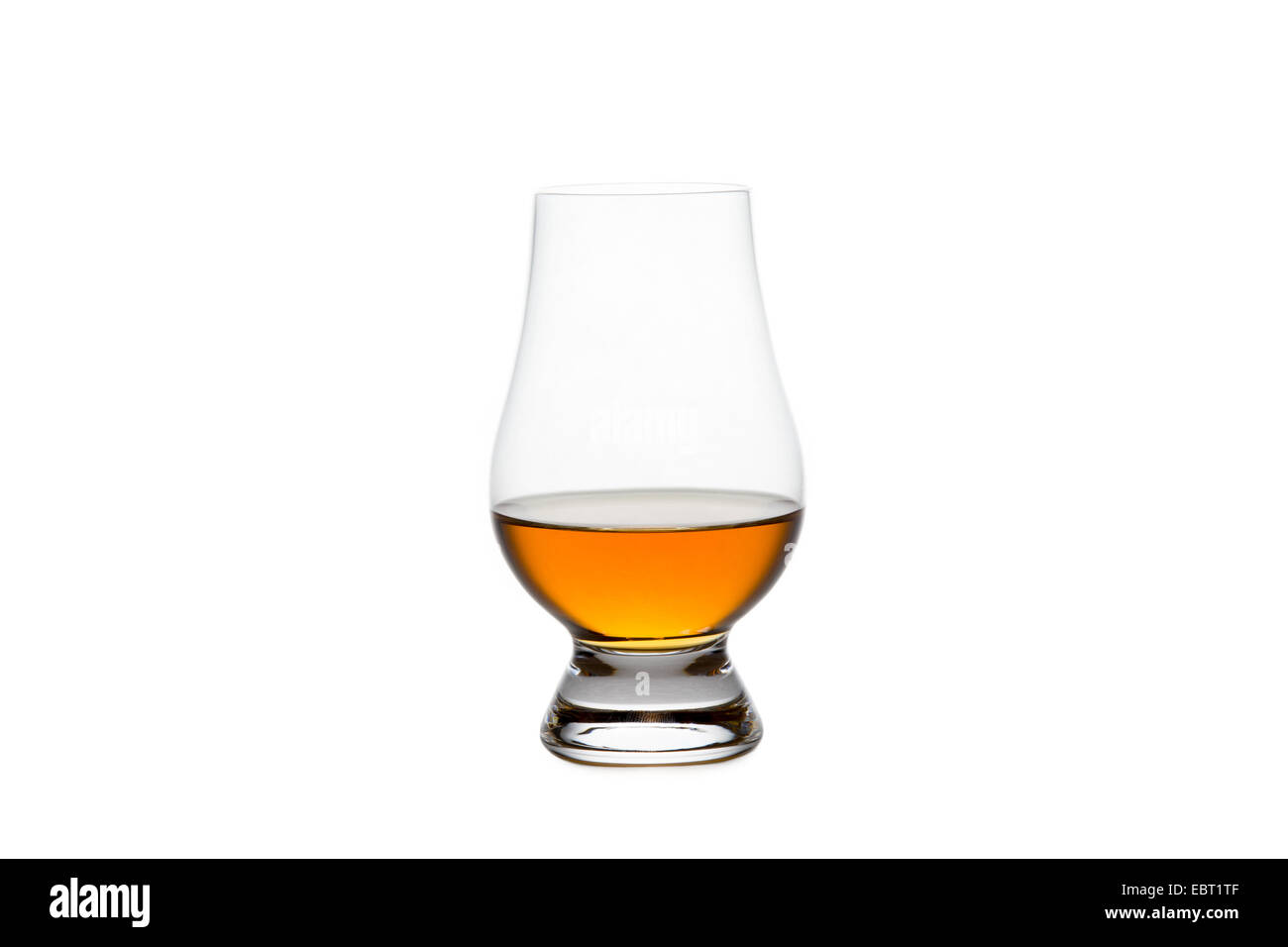 Crystal glass containing whiskey, bourbon, or other amber liquor.  Isolated on white. - Stock Image