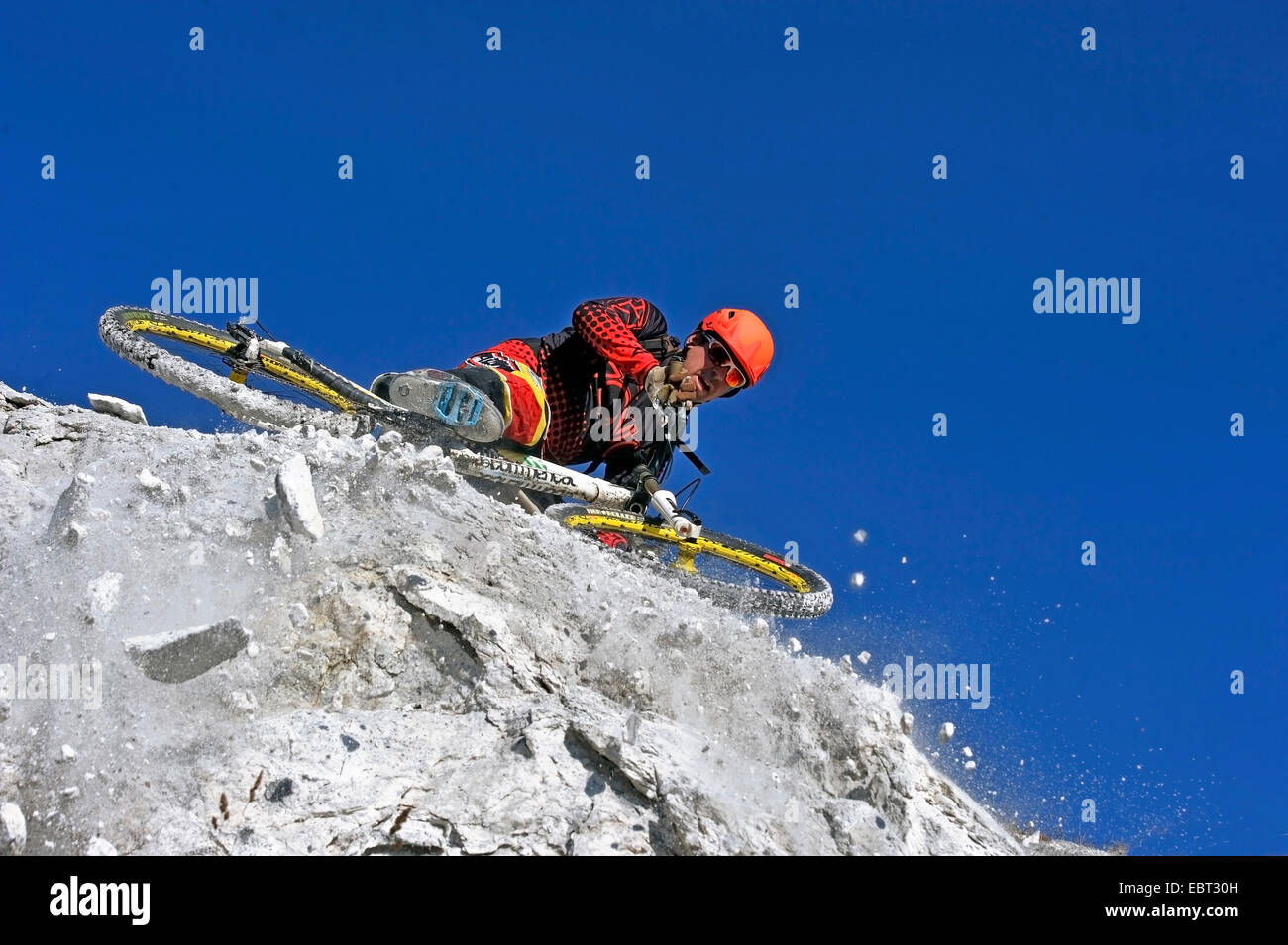 daring mountain biker stopping at a rocky abyss, France, Savoie - Stock Image