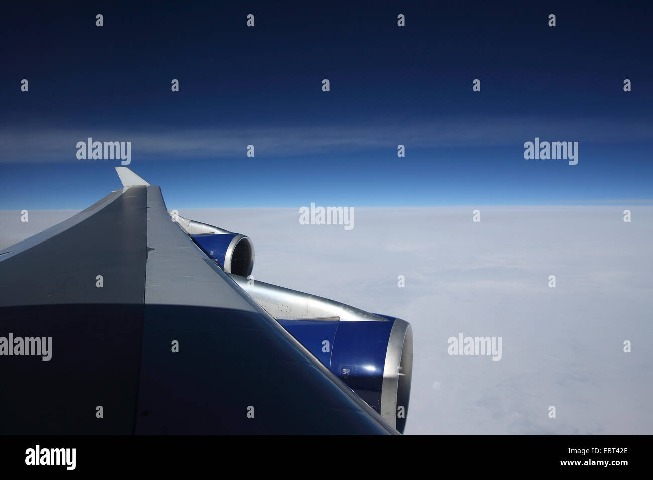 view through a wing of airplane Boeing 747 to the clouds and the sky - Stock Image