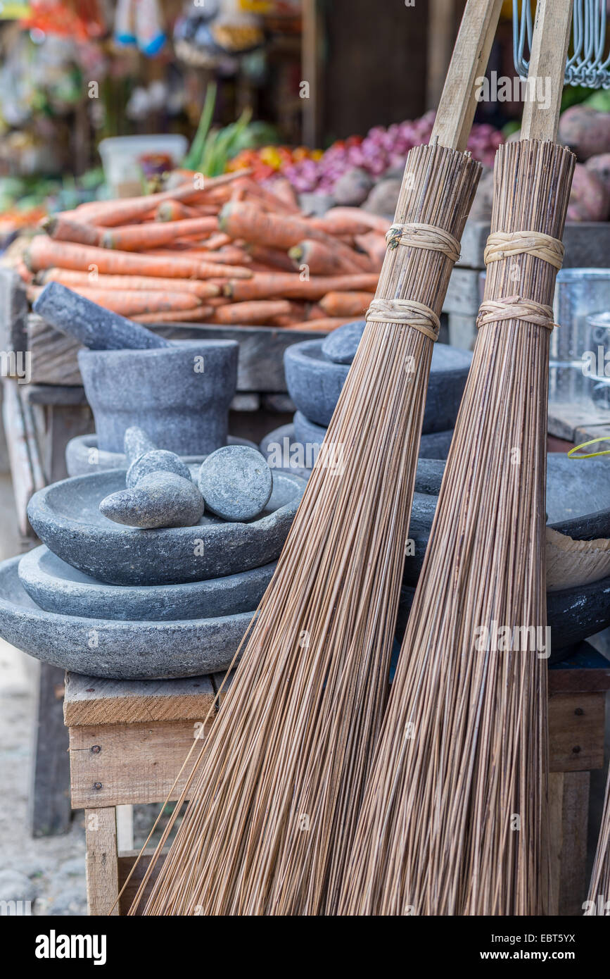 Selective focus on group of old fashioned straw brooms for sell in asian market. Stone mortars and vegetables in - Stock Image