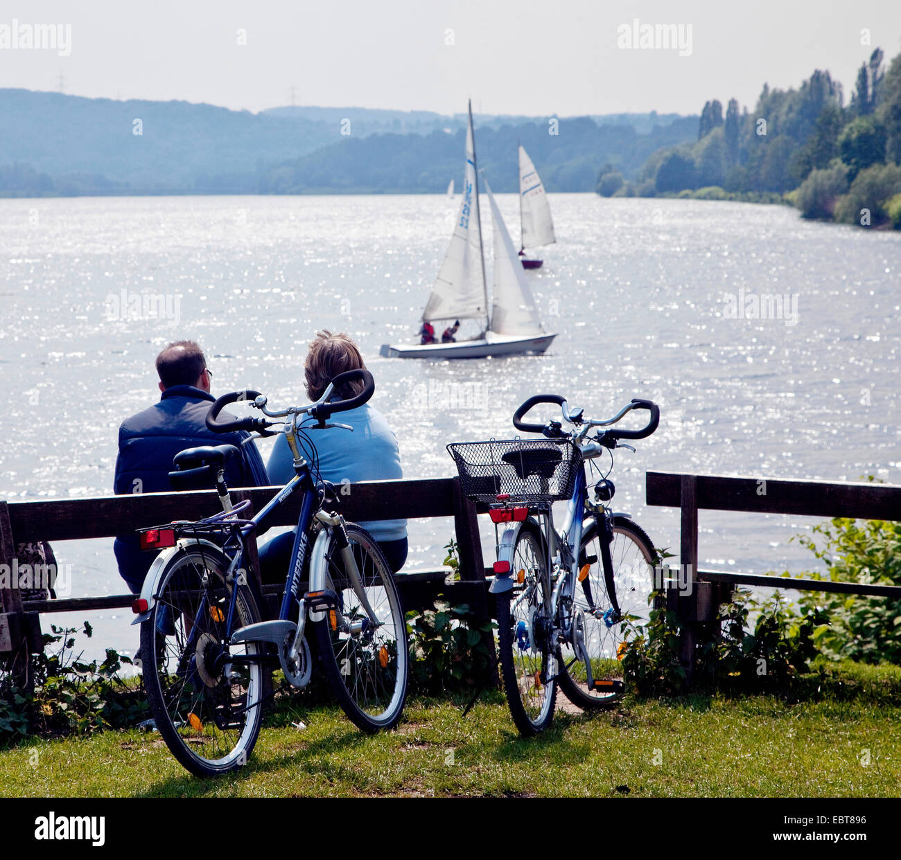 couple with bikes sitting on a bench watching at the Lake Kemande, Kemnader See, Germany, North Rhine-Westphalia, - Stock Image