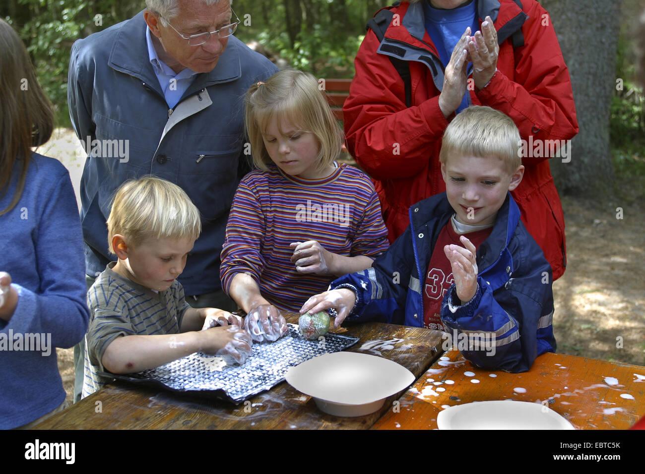children felting sheep wool, Germany - Stock Image